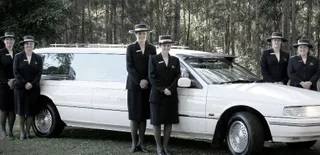 White hearse with female funeral team