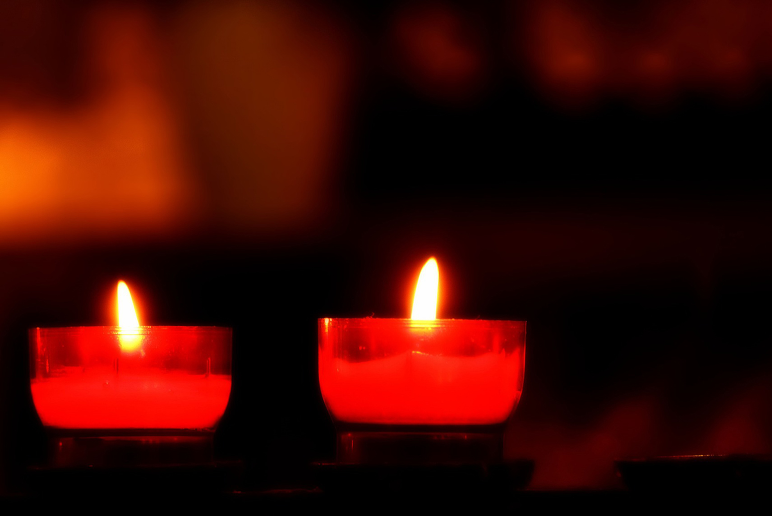 Candles with reddish hue on a hazy dark background